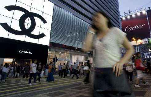 Pedestrians walks past the Chanel SA logo which is displayed on one of the company's stores in Hong Kong, China, on Saturday, Oct. 8, 2011. Hong Kong retail sales, boosted by mainland Chinese tourists, surged 26 percent to HK$264 billion ($34 billion) in the eight months through August. Photographer: Jerome Favre/Bloomberg via Getty Images